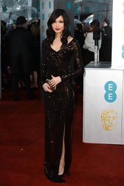 Gemma Chan chose to simply shine at the BAFTAs in this glittering long-sleeve gown with a bronze sheen. She finished the look with red lips and soft waves.