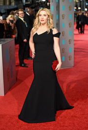 Kate Winslet added some color with a flower-embellished red clutch.
