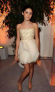 Isabelle Fuhrman wears a darling gold and ivory strapless cocktail dress with layers of chiffon petals around the skirt.