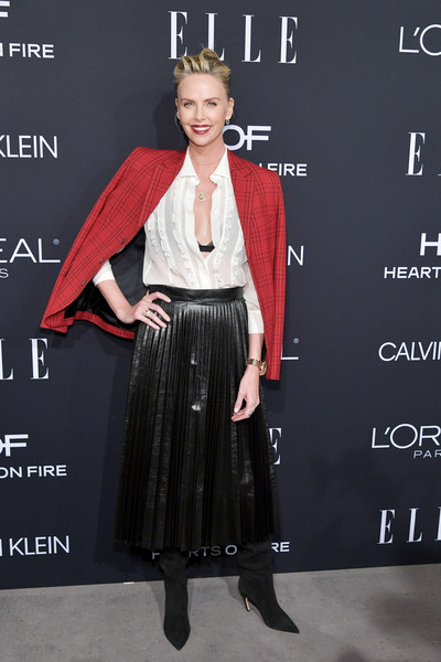 Charlize Theron completed her outfit with a pleated black skirt.