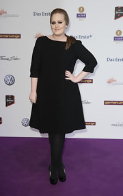 Adele paired her LBD with black patent pumps and opaque tights.