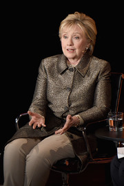 Hillary Clinton paired a gold coat with beige trousers for the Women in the World Summit.