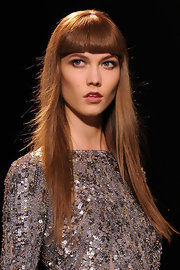 Karlie Kloss walked the runway at the Elie Saab fashion show with her long hair styled sleek and straight with heavy blunt bangs.