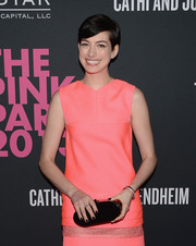 Anne Hathaway complemented her coral dress with an oval black hard-case clutch by Edie Parker when she attended the Pink Party.