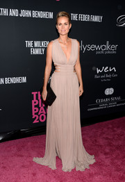 Laeticia Hallyday looked like a goddess during the Pink Party in a gorgeous nude evening dress with waist cutouts and a plunging neckline.