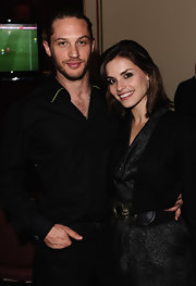 Tom Hardy punctuates an all black look with gold piping on the collar of his button-down shirt.