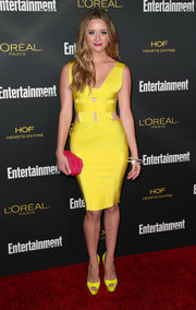 Greer Grammer sported a striking color combo with this geometric fuchsia Blumera clutch and yellow bandage dress ensemble.