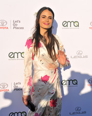 Jordana Brewster paired a black hard-case clutch with a floral wrap dress for the 2017 EMA Awards.