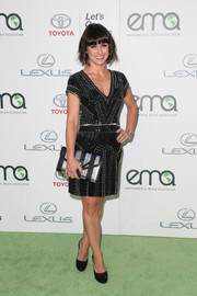 Constance Zimmer matched her dress with a silver and black striped envelope clutch.