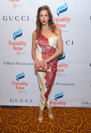 Alysia Reiner coordinated her jumpsuit with a cream and red print clutch.