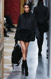 Chanel walks the runway in a black down jacket lined with fur.
