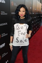 Jeannie Mai looked funky at the Escape to Total Rewards event in a black leather shrug sweater layered over a tank top.