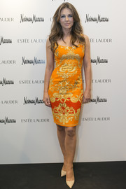 Elizabeth Hurley looked ageless in a curve-hugging orange print dress during the Estee Lauder shop opening.