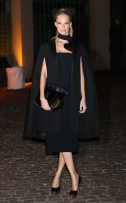 Poppy Delevingne looked dramatic in a black satin-lapel cape layered over a navy dress during the Global Fund event.