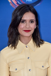Nina Dobrev brightened up her beauty look with a swipe of bold red lipstick.