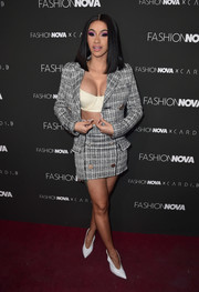 Cardi B went for a business-meets-sexy look with this gray tweed skirt suit and cream bra combo at the launch of her collaboration with Fashion Nova.