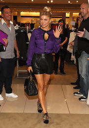 Fergie wore a purple silk button-down with a sexy key-hole opening for her shoe launch at Nordstrom.