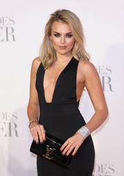 Tallia Storm accessorized with a black patent clutch by Louis Vuitton at the UK premiere of 'Fifty Shades Darker.'