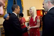 Michaele wears several layered gold bracelets, while shaking hands with President Obama.