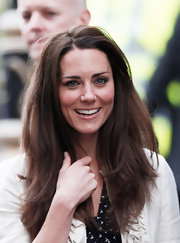 Kate Middleton added shine to her lips with pale pink lipgloss.