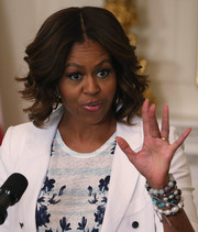 First Lady Michelle Obama styled her hair in wavy tresses with a center part.