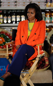 Michelle Obama looked vibrant at the California FreshWorks Fund event in a neon-orange pea coat layered over a yellow blouse.