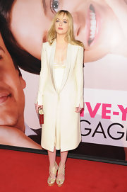 Dakota Johnson added to her monochromatic ensemble with a pair of pale gold satin heeled sandals.