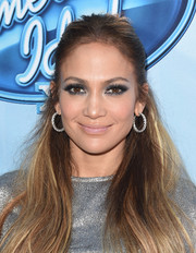 Jennifer Lopez teamed big diamond hoops with her silver lamé shirt for total shimmer.