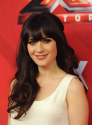 Zooey Deschanel wore her long hair with sexy lash-grazing bangs and loads of loose curls during 'The X Factor' season finale.
