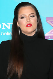 Khloe wore her famous Kardashian tresses in a side-swept half-up 'do.