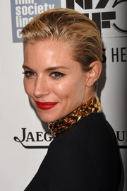 Sienna Miller added a bold red lip to her dark ensemble at the 52nd New York Film Festival.