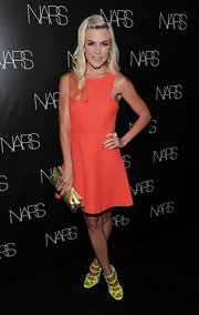 Tinsley Mortimer added sheen to her full orange frock with a metallic gold clutch.