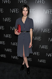 Alexa Chung added the perfect pop to her look with a red leather clutch.