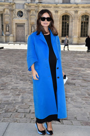 Miroslava Duma hid her baby bump in a bulky blue wool coat by Christian Dior during the label's fashion show.