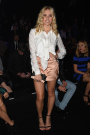 Pixie Lott attended the Just Cavalli fashion show wearing a laser-cut white ruffle blouse from the brand.