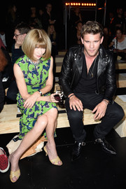 Anna Wintour attended the Saint Laurent fashion show looking bright in a green and blue print dress.