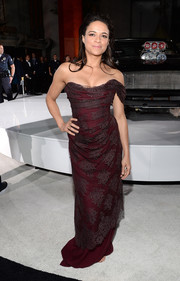 Michelle Rodriguez looked phenomenal at the 'Furious 7' LA premiere in a burgundy Vivienne Westwood corset gown featuring an elegant lace overlay and draped shoulder detailing.