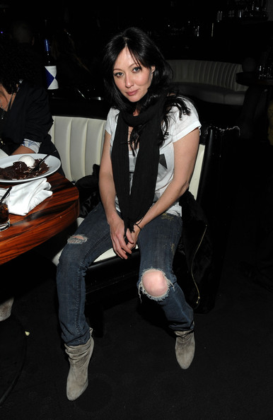 Shannen's olive suede boots add a hint of elegance to her ripped jeans and white tee look.