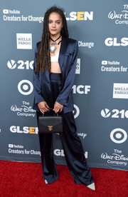 Sasha Lane rounded out her look with a black leather purse.