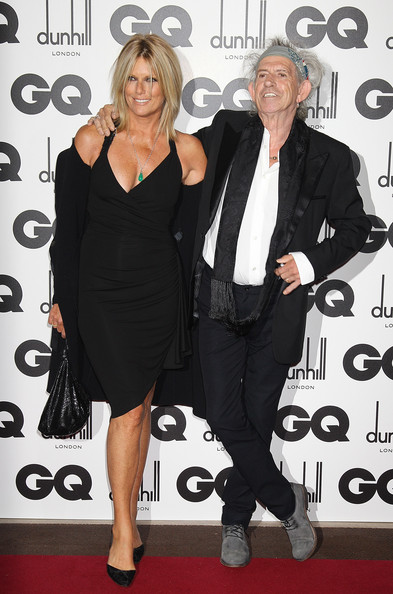 Patti Hansen attended the GQ Man of the Year Awards wearing a black fitted knee-length deep V-neck wrap dress.