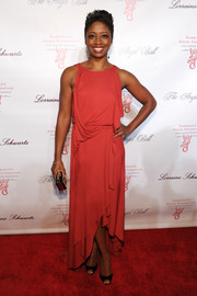 Montego Glover chose a draped coral fishtail dress for her Angel Ball red carpet look.
