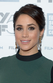 Meghan Markle contrasted her heavy eye makeup with a glossy pale-pink lip.