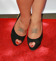 Kelly has two skulls tattooed on the top of her feet. The right tattoo features a pink bow while the other has a yellow mohawk.