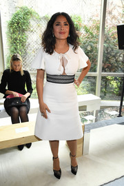Salma Hayek attended the Giambattista Valli fashion show wearing a white midi dress with a peekaboo bodice and a contrast waistband.