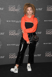 Ella Eyre went the sporty route in a hooded orange shrug sweater at the Gigi Hadid x Maybelline party.