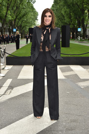 Carine Roitfeld suited up in sexy style with this Giorgio Armani pinstripe pantsuit teamed with a see-through top for the brand's 40th anniversary reception.
