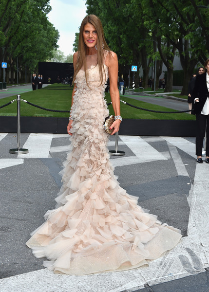 Anna dello Russo complemented her gown with a metallic clutch in two shades of gold.