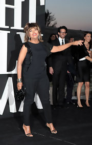 Tina Turner kept her look classic and sophisticated with a dark blue top with sequined ruffled sleeves.