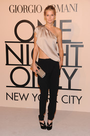 Toni Garrn attended the Giorgio Armani SuperPier show wearing black slacks with a belly-baring one-shoulder top.