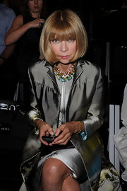 Anna Wintour paired her silver trench coat with a gemstone statement necklace.
